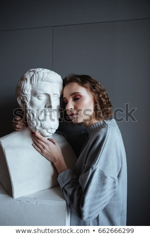 close up of a woman leaning on a marble bust stock photo © deandrobot
