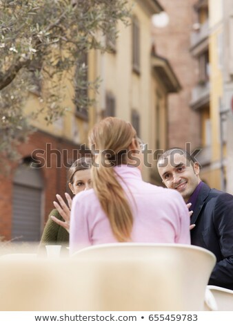 Friends sitting at a cafe in a piazza Stock photo © IS2