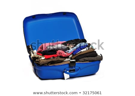 A woman pressing on a suitcase full of clothes Stock photo © IS2