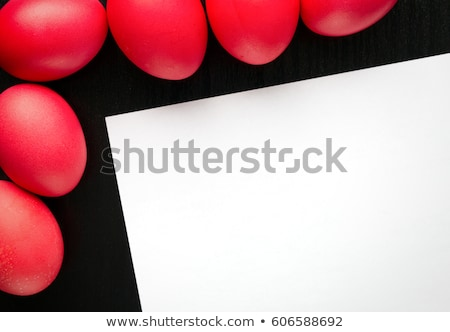 top view of red easter egg on black plate on white stock photo © lightfieldstudios