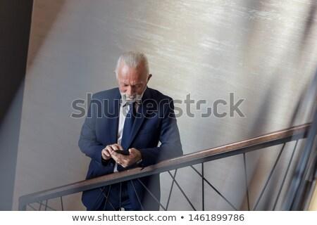 Senior businessman on mobile walking Stock photo © IS2