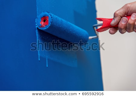 Decorator painting a wall with a paint roller Stock photo © stokkete