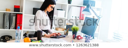 A young girl stands near a table and prints on the keyboard. Before the girl is a magnetic board and Stock photo © Traimak