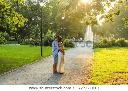 Beautiful smiling love couple sitting near fountain outdoors Stock photo © boggy