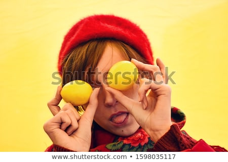 beautiful woman covering eyes with citrus lemons posing isolated over yellow wall background stock photo © deandrobot