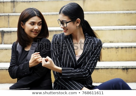Image of two beautiful women smiling and hooking each others lit Stock photo © deandrobot