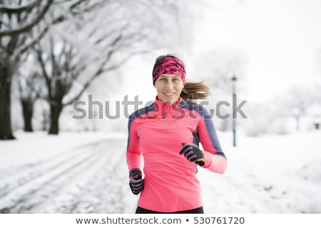 Woman Running in Snowy Park in winter season Stock photo © Lopolo