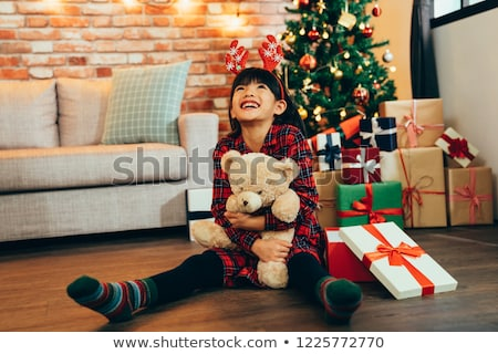 Stock photo: girl in red dress hugging teddy bear at home