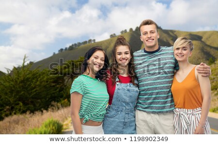 happy friends hugging over big sur hills and road Stock photo © dolgachov