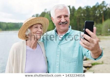 happy romantic senior couple in casualwear making selfie stock photo © pressmaster