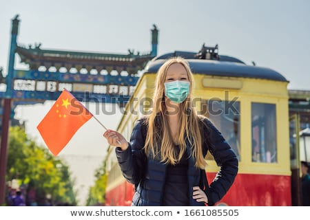 Enjoying vacation in China. Young woman with national chinese flag on the background of the old Chin Stock photo © galitskaya
