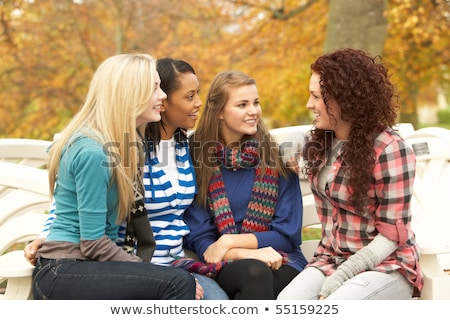 Group Of Four Teenage Girls Sitting And Chatting On Bench In Aut stock photo © monkey_business