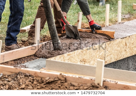 Construction Worker Leveling Wet Cement Into Wood Framing Stock photo © feverpitch