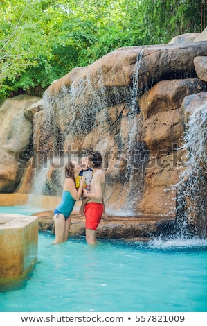 happy family mother father and son relaxing under a waterfall in aquapark stock photo © galitskaya