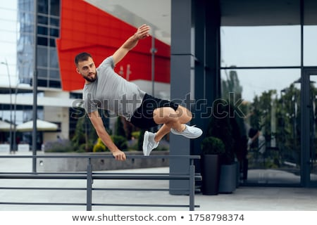 Image of young athletic man in sportswear jumping while working out Stock photo © deandrobot