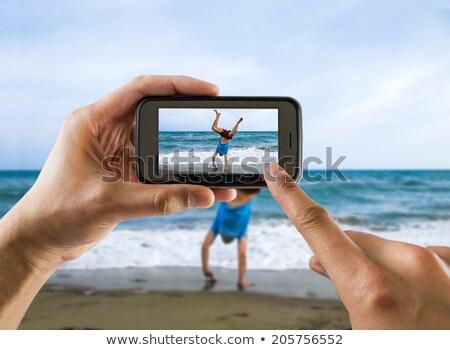 man using video camera at the beach stock photo © iofoto