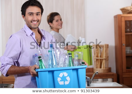 a young couple recycling plastic in their kitchen Stock photo © photography33