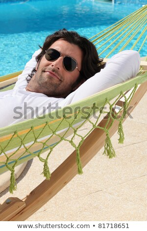 Man laid in hammock by swimming pool Stock photo © photography33