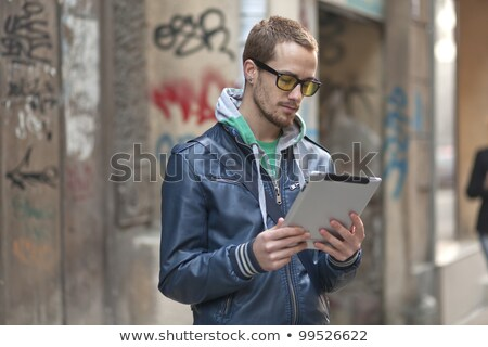 Young man with glasses and tablet computer on street stock photo © adamr