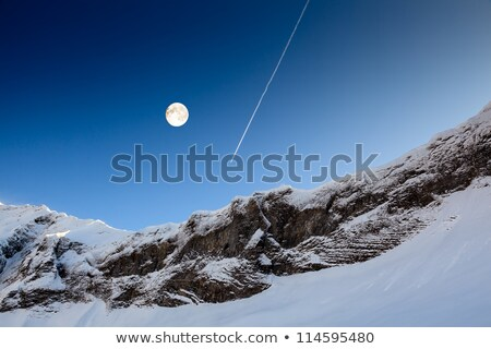 full moon and airplane trail in blue sky above mountain peak fr stock photo © anshar
