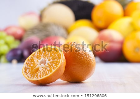 Close up photo of edible fruits - a orange on a solid  bright blue wooden table Stock photo © MamaMia