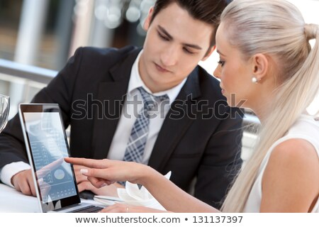 Young business partners reviewing work at lunch. Stock photo © nenetus