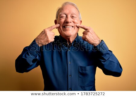 Senior man standing with finger in mouth Stock photo © bmonteny