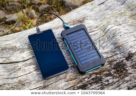 charging mobile phone with solar charger stock photo © adamr