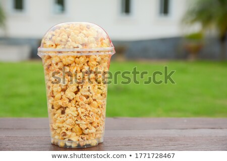 Delicious popcorn in paper pack on wood table  Stock photo © nalinratphi