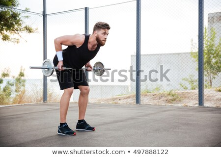 Full-length portrait of a muscular man working out with dumbbells on white background Stock photo © deandrobot