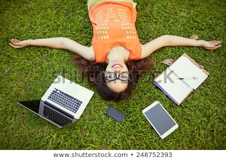 Happy young beautiful woman lying on the grass with laptop and red flower. Sunny day. Stock photo © deandrobot
