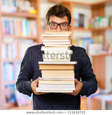 Stock photo: Surprised male student holding book