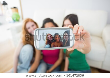Woman sitting on a sofa taking a photo of themselves Stock photo © wavebreak_media