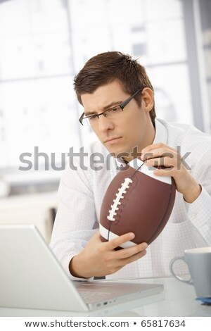 Businessman concentrating on work, holding football Stock photo © nyul