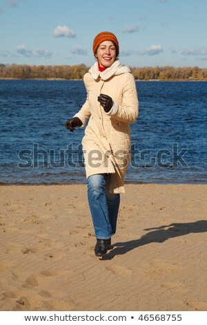 Girl runs along beach autumn day. Front view in full growth. Stock photo © Paha_L