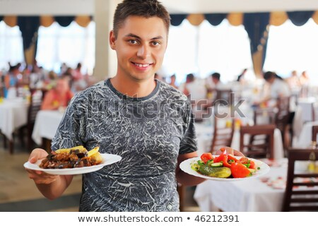 young smiling man with two dishes in hands at restaurant stock photo © paha_l