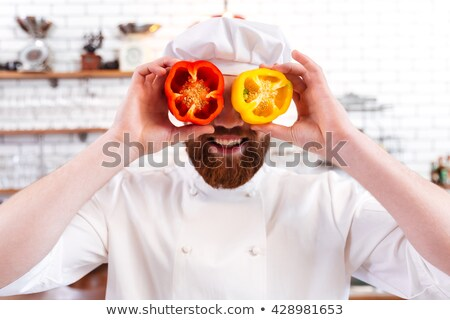 Chef holding bell peppers halves in front of his eyes  Stock photo © deandrobot