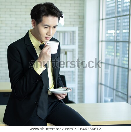 happy young asian man looking at camera while drinking coffee stock photo © deandrobot