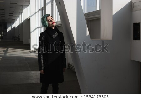 Woman in red coat standing with eyes closed at corridor Stock photo © deandrobot