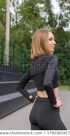 Strong fitness lady make sport stretching exercise in gym. Stock photo © deandrobot