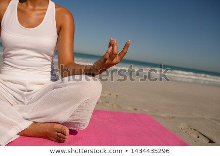 Low section of man doing meditation at beach stock photo © wavebreak_media