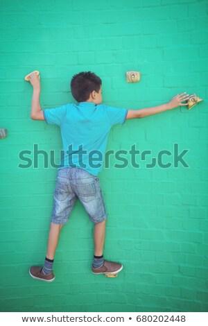 Garçon escalade vert mur ciel Photo stock © wavebreak_media
