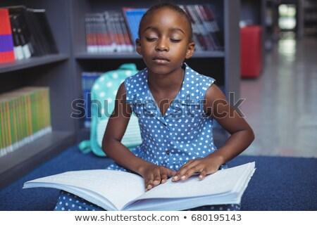Girl reading braille at desk in library Stock photo © wavebreak_media