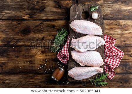 Raw turkey wings on wooden background top view, flat lay Stock photo © yelenayemchuk