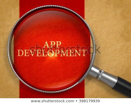 App Development through Loupe on Old Paper. Stock photo © tashatuvango