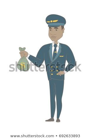 Young african-american pilot holding a money bag. Stock photo © RAStudio