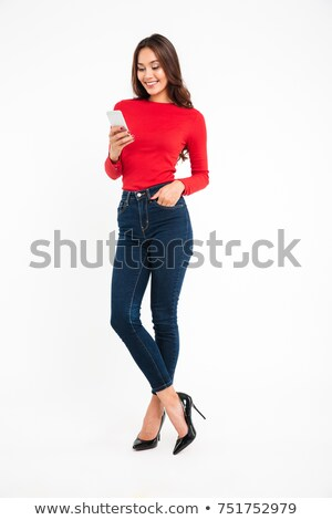 Full length portrait of a happy satisfied asian woman texting Stock photo © deandrobot