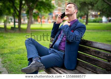 businessman on bench, adjusting tie Stock photo © IS2