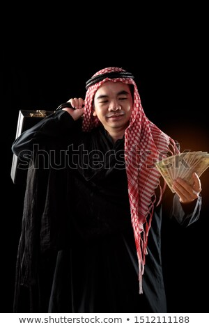 Arabic businessman holds suitcase with money Stock photo © studioworkstock