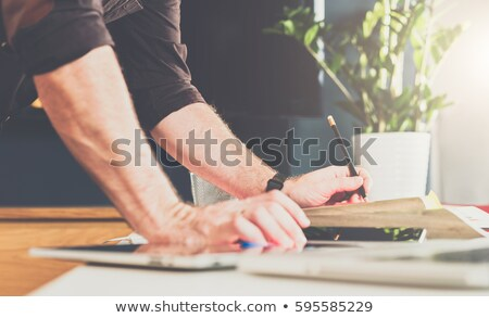 Сток-фото: A Young Man Stands Near A Table In The Office Holds A Pencil In His Hand And Works With Documents A